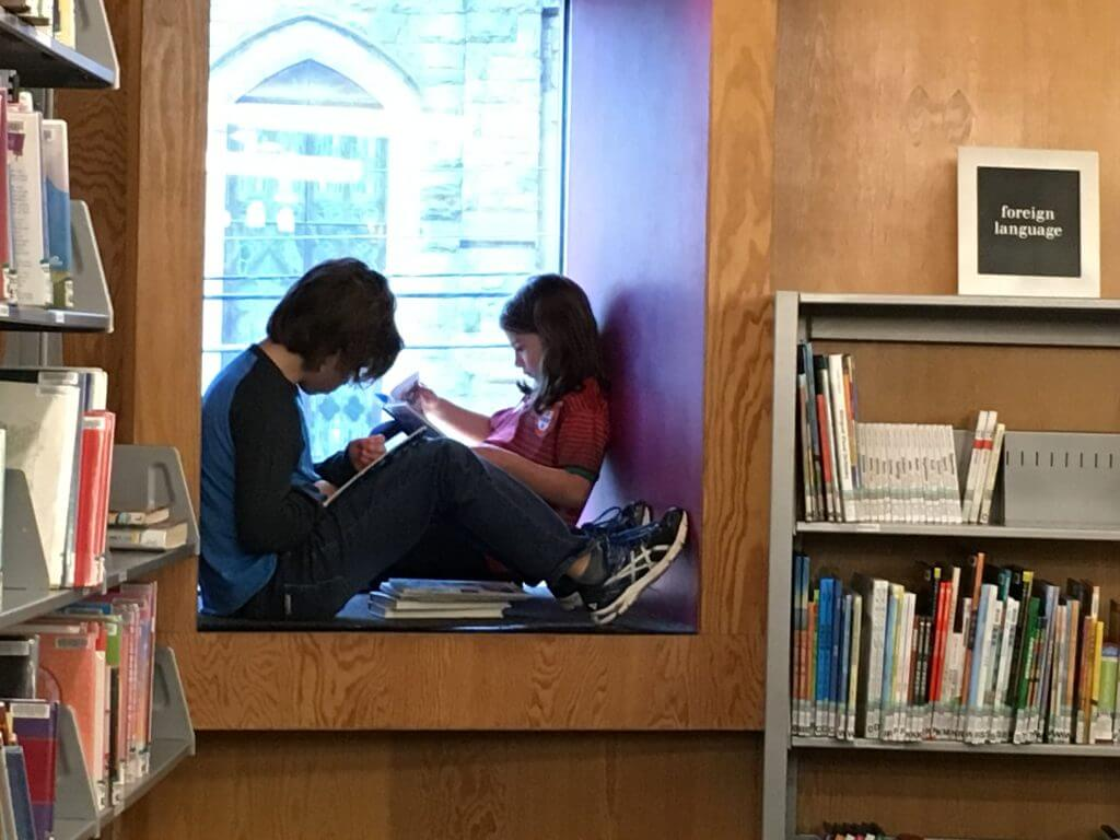 Two children enjoy reading in the window seat at CLP - Squirrel Hill.