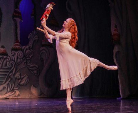 A ballet dancer holds up a nutcracker
