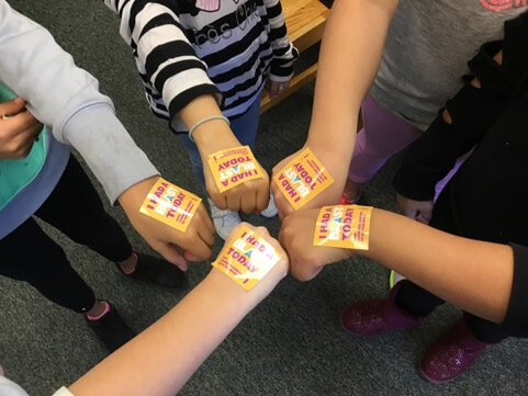 "Fourth grade students at PPS Brookline show off their ""I Had a BLAST Today with Carnegie Library of Pittsburgh"" stickers."