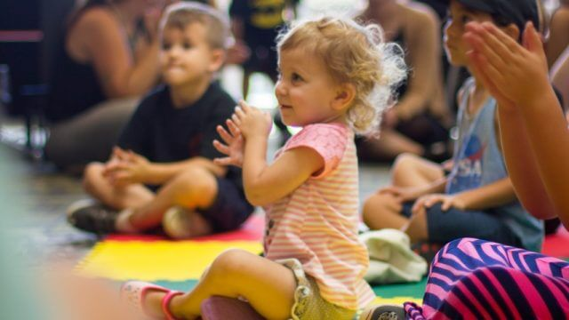 Several children sit on the floor and clap while listening and watching something