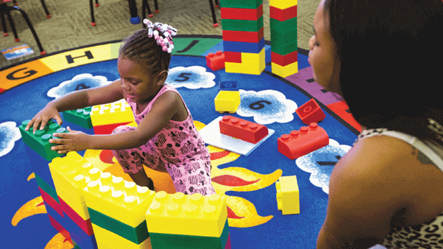 Little girl plays with building blocks at the library.