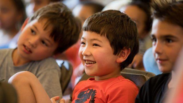 three children sit listening to someone talk, while one child laughs