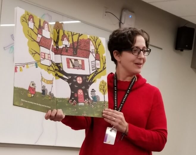 Early Learning BLAST Outreach Specialist Korie reads a book during a professional development workshop.