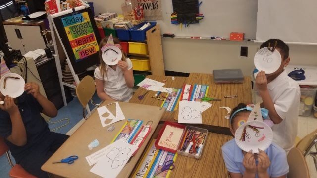 Four third graders hold a paper plate craft up to their faces in a classroom