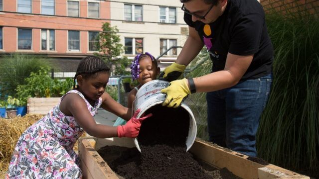 Two children and a librarian add soil to a raised garden bed at CLP-Hazelwood