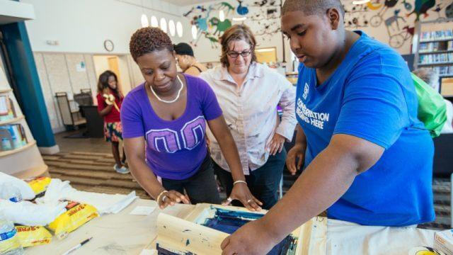 A teen, an adult and a library volunteer screen print a t shirt