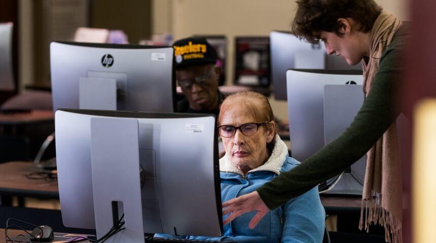 Librarian helping a patron during a computer class.