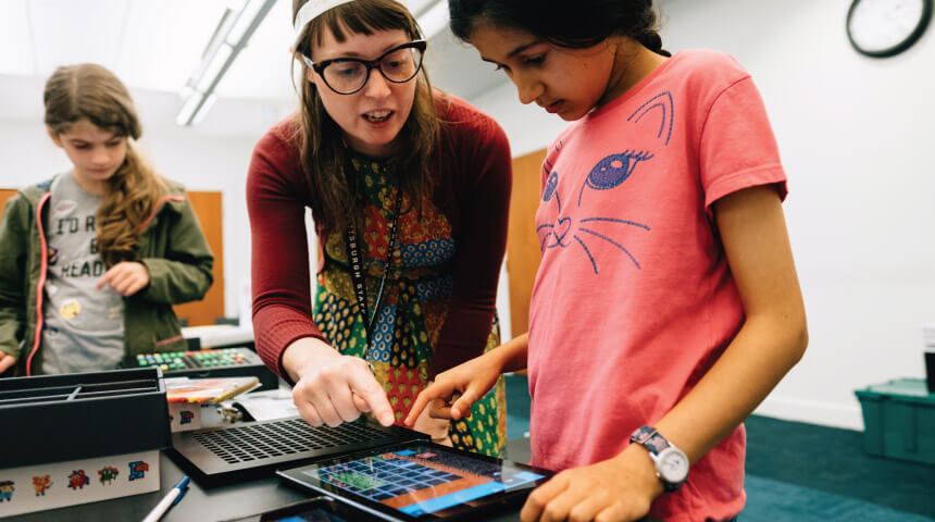 Librarian explains coding activity on a tablet to a young girl