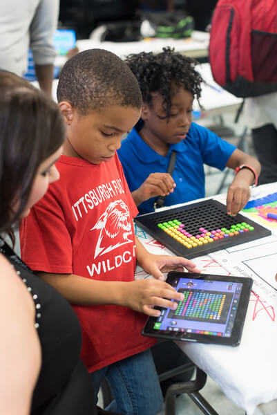 Kids explore a coding app on an iPad.
