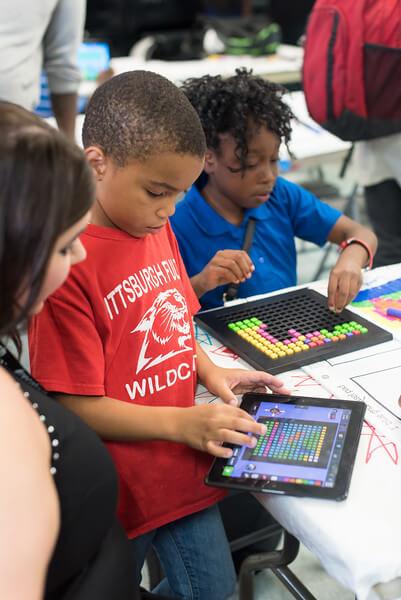 Kids explore a coding app on an iPad.