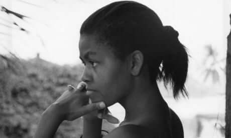 Profile portrait of young Michelle Obama in black and white staring off into the distance