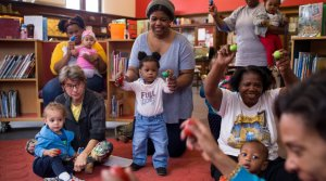 Caregivers and children use egg shakers in storytime