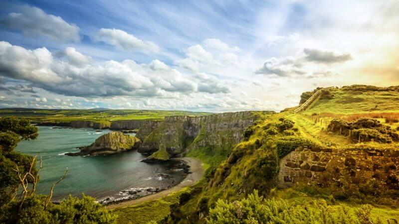 Picture of lush, green hills, countrysides, and cliffs, leading into a blue sea on a bright and cloudy day