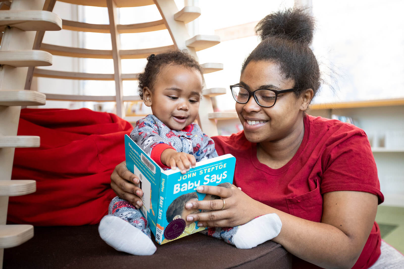 Mother reads book to baby in library