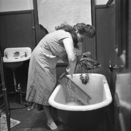 Mrs. Pagone hand washes her laundry in 1952.