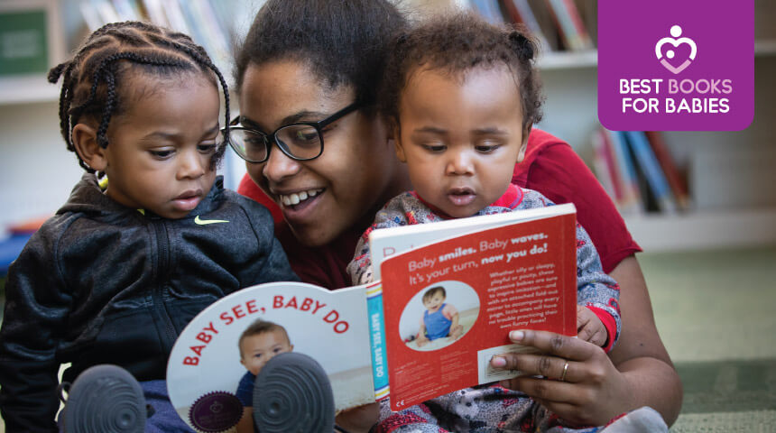 parent reads book to two young children