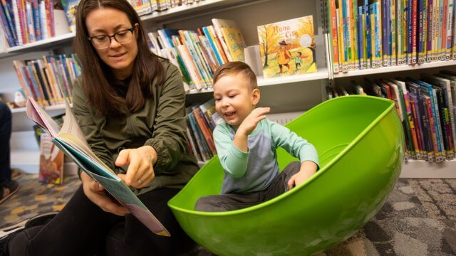 A young boy in a rocking bowl is being read to by a caregiver.
