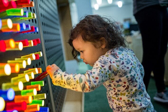 Young child plays at the light wall.