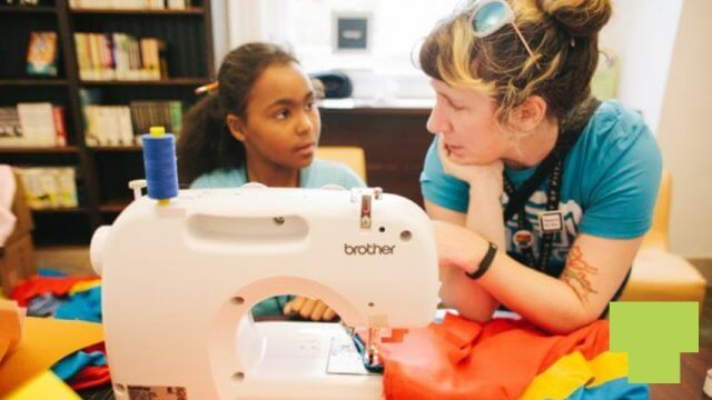 Teen specialist helps a teen at a sewing machine
