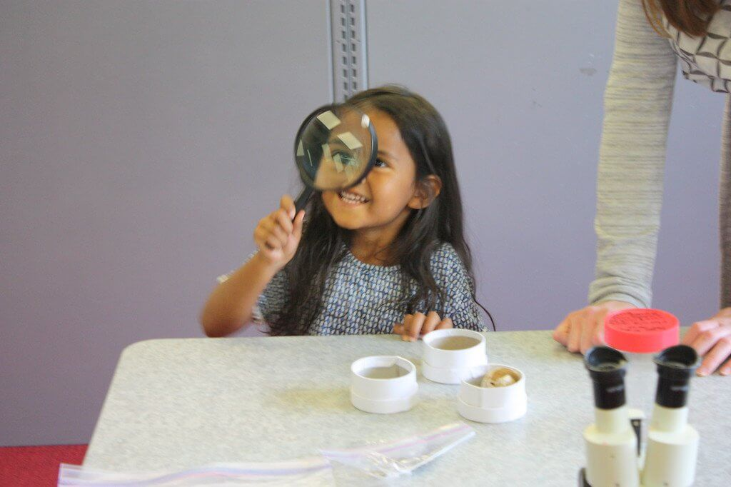 A child gets an up-close view of the world with her magnifying glass.