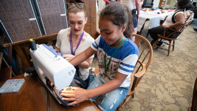 A volunteer helps a teen with a sewing machine