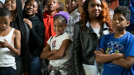 Nine African American kids and teens stand together