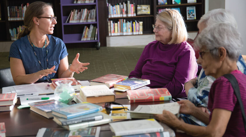 Adults gathered at a book club in the library.