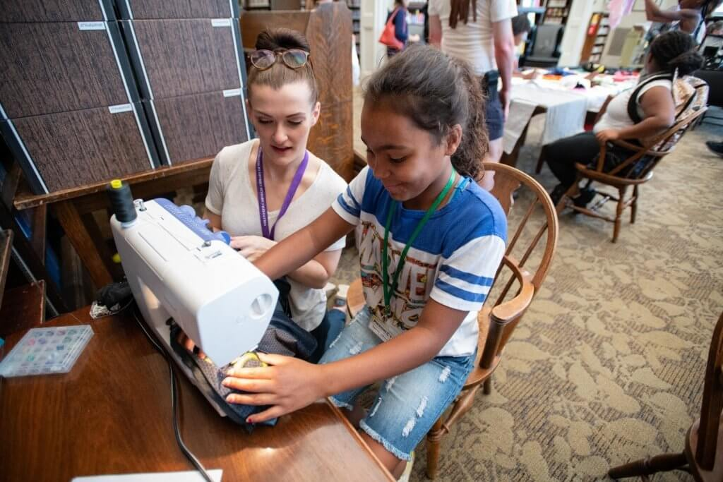 Teens work on a sewing machine.