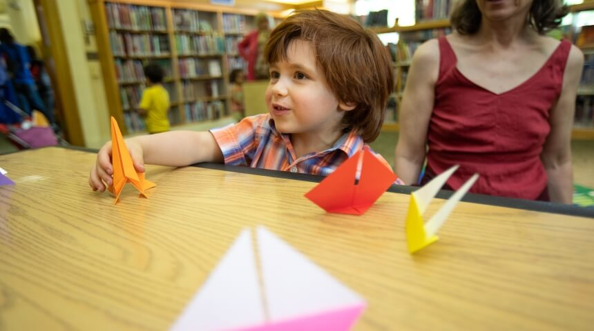 Child playing with origami crafts on a tabletop.