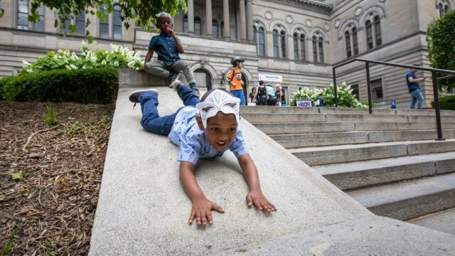 Kids playing on the steps of the Carnegie Library of Pittsburgh Main branch in Oakland.