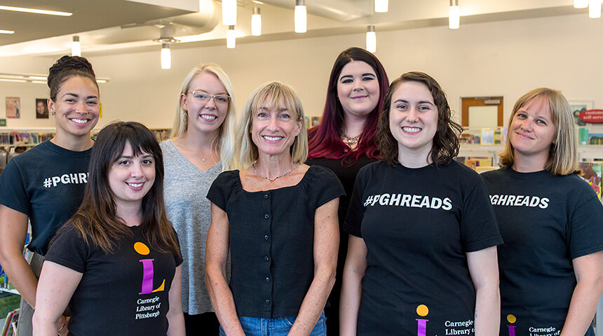 Seven librarians stand in front of books shelves