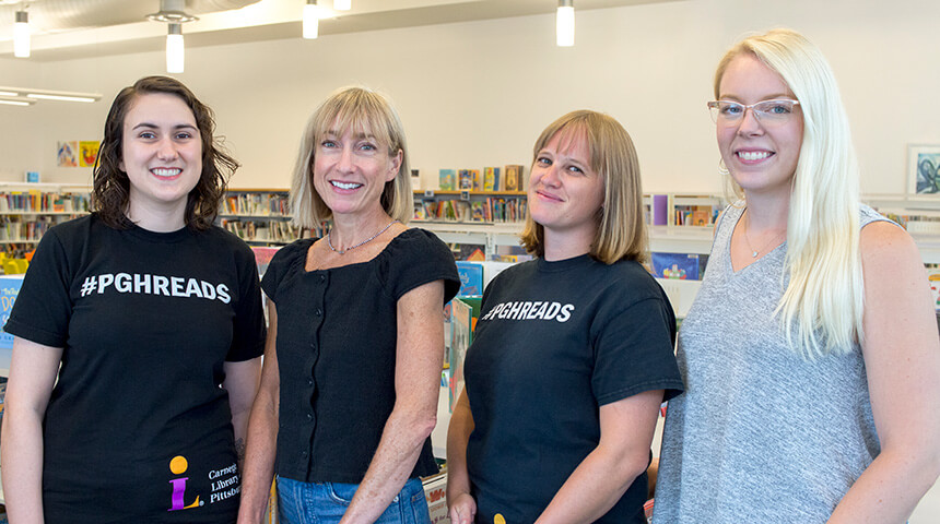 Four librarians stand in front of shelves of books