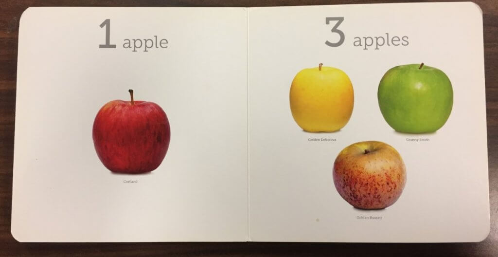 """Two-page spread from Edible Numbers featuring a single red apple and the text """"1 apple"""" on the left-hand page. On the right-hand page, there are three apples, one yellow, one green, and one red, with the text """"3 apples"""" above."""