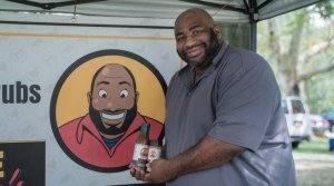 412 BBQ owner Jamal Etienne-Harrigan shows off his sauces in his tent at a farmers' market