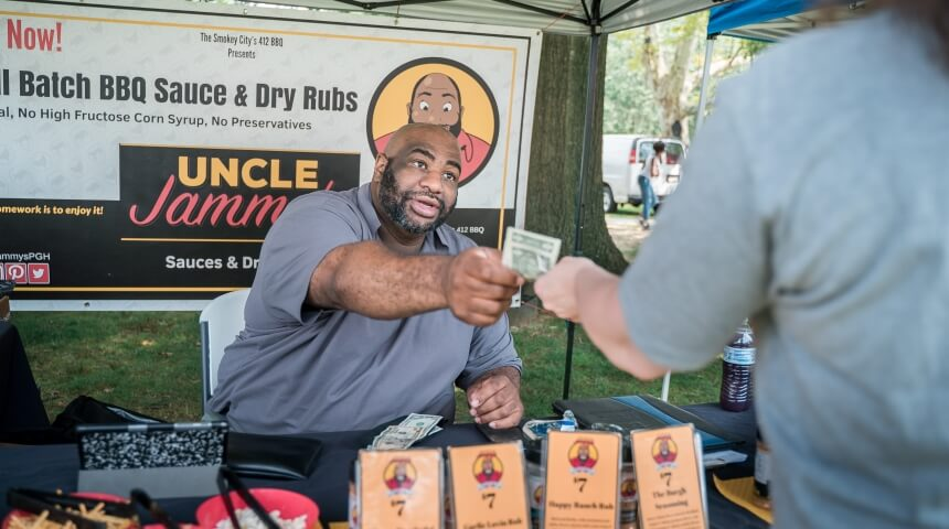412 BBQ owner Jamal Ettiene-Harrigan assists a customer with a purchase at his tent at a farmers' market