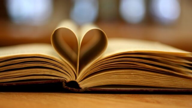 A book lays open on a table with some of the pages folded back to make a heart
