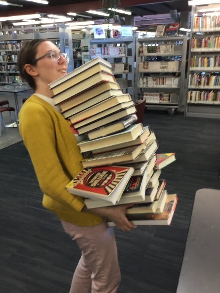 A teen carries a very big stack of books.