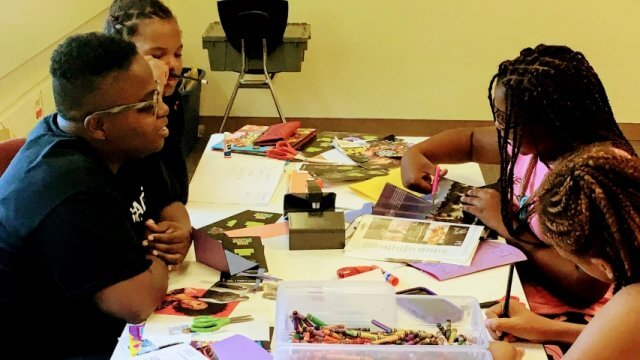 Library staff member and teens working on a craft at an outreach visit.