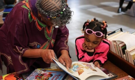 Adult and young child read a book together