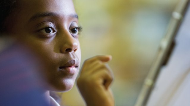 A young black child looks at a the screen