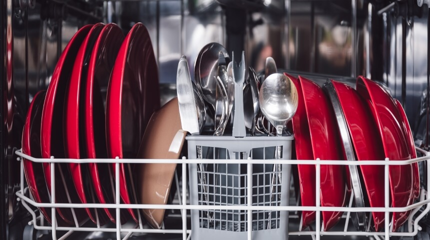 Lower rack of dishwasher filled with dishes and silverware.