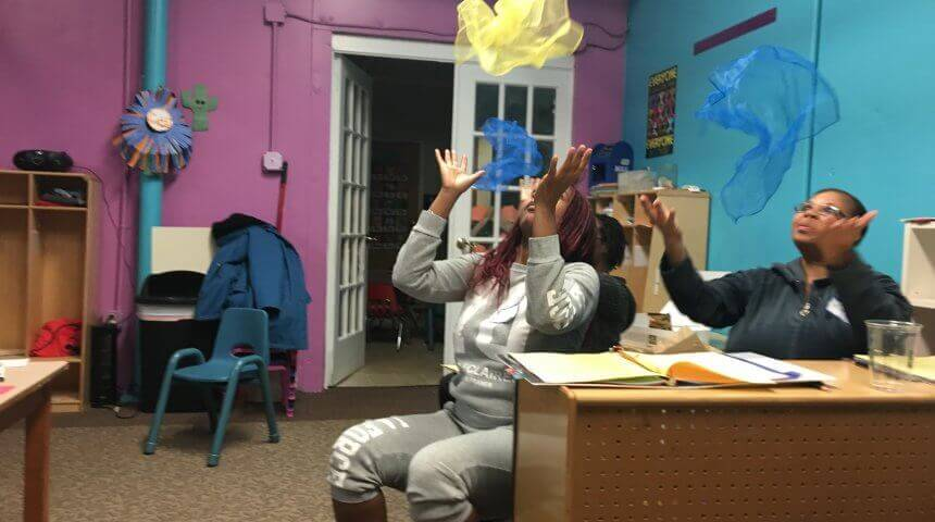 "Two Kidsville Daycare teachers throw sheer fabric into the air as part of the storytime song ""Popcorn Kernels"""