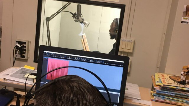 Former Pittsburgh Pirate Andrew McCutchen narrates an audiobook. Volunteer monitors recording outside of booth.