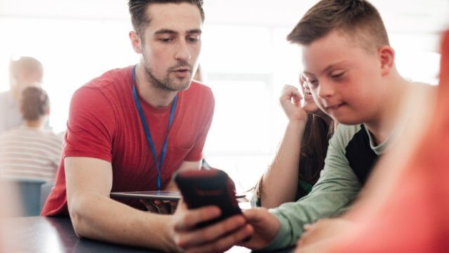 Teacher and student look at a mobile device together