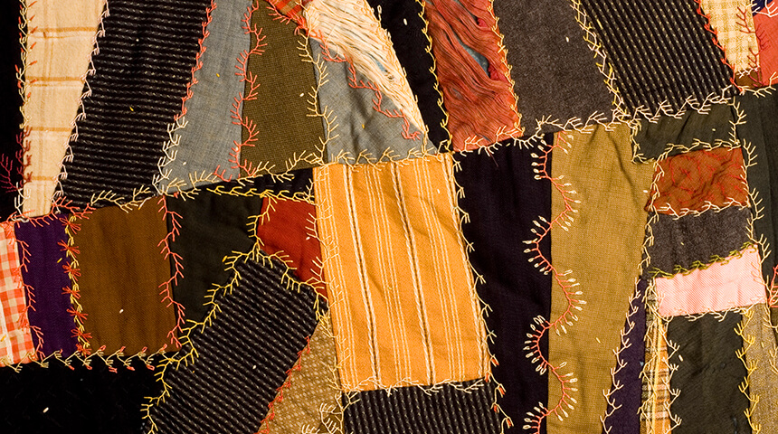 Asymmetrical patchwork antique quilt with hand embroidery.