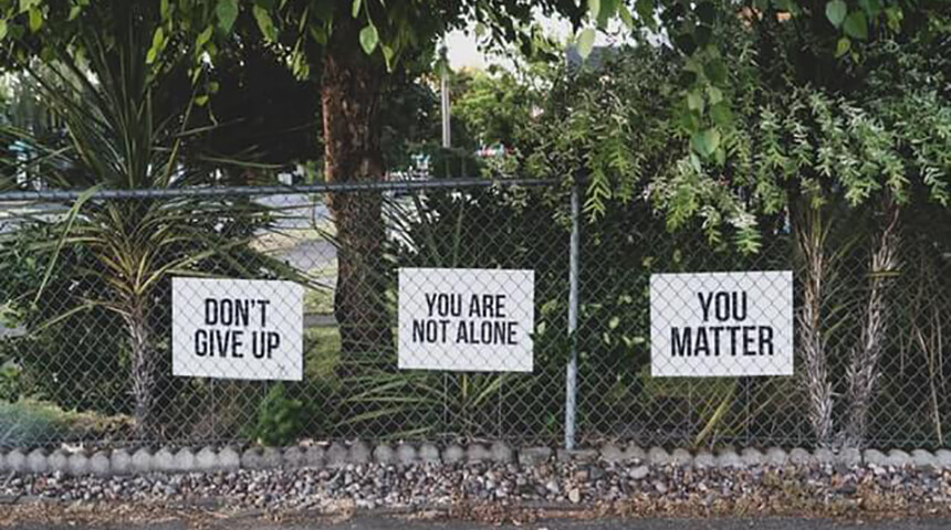 A metal fence with signs reading: Don't Give Up, You Are Not Alone, You Matter