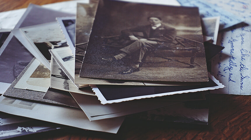Pile of old family photographs including one with a man sitting on black chair in gray scale.