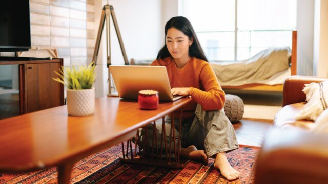 Woman sitting on floor looking at a laptop on a coffee table.
