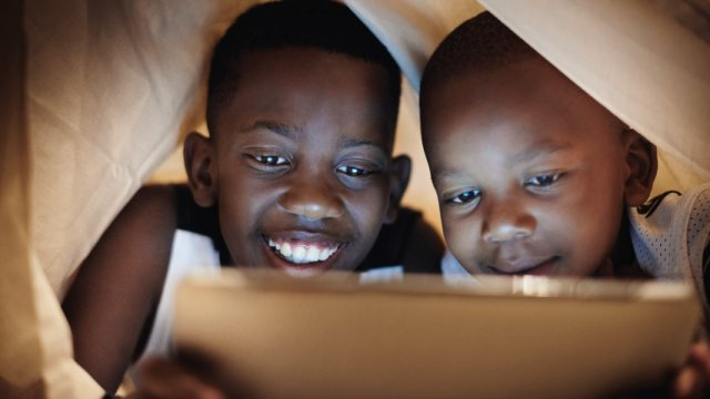 Two young boys look at a tablet while under a blanket