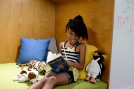 A child reads a book in a cozy corner with pillows and stuffed animals